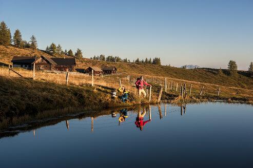 Austria, Altenmarkt-Zauchensee, young couple at mountain lake in the Lower Tauern - HHF005144