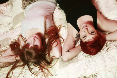 Portrait of two female friends relaxing on a blanket at home - VEF000043