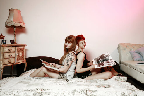Portrait of two female friends with magazines sitting back to back on a blanket at home - VEF000047
