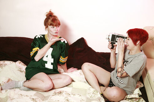 Woman filming her female friend with super 8 mm camera at home - VEF000045