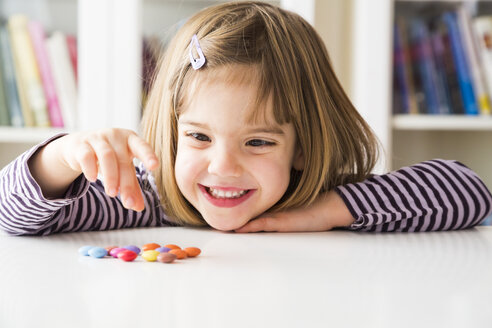Smiling little girl playing with chocolate buttons - LVF003030