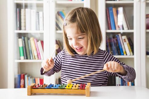 Portrait of happy little girl playing xylophones - LVF003041