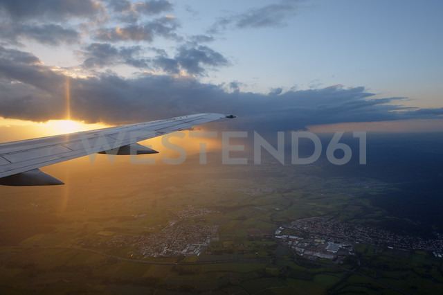 Germany, wing of an airplane with clouds at sunset - RUEF001522