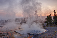 USA, Wyoming, Yellowstone National Park, steam rising up from Firehole Spring at sunrise - RUEF001581