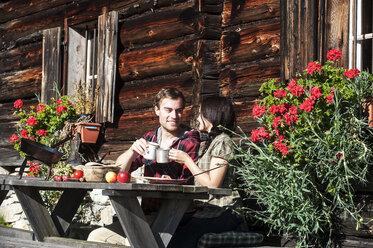 Austria, Altenmarkt-Zauchensee, couple having a break at alpine cabin - HHF005152