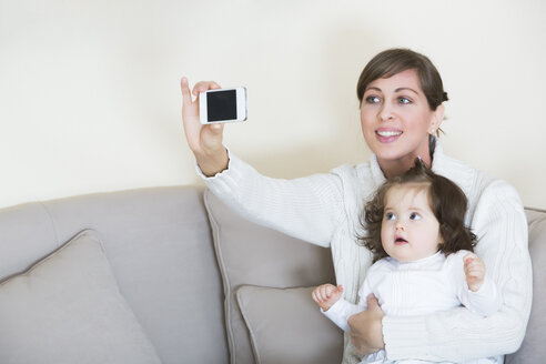 Woman taking selfie with her daughter on couch - JTLF000062