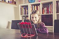 Little girl using digital tablet in front of bookshelf - SARF001496