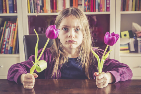 Portrait of pouting little girl with two tulips in her hands - SARF001498