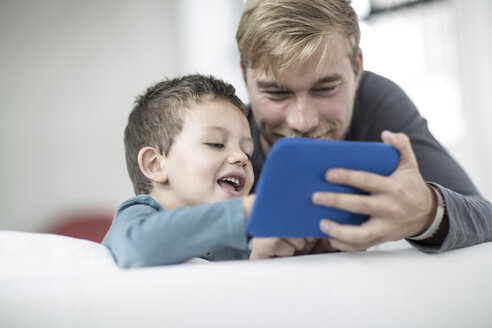 Father and little son on couch looking at a tablet - ZEF004010