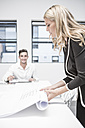 Businesswoman in office rolling up constuction plan - ZEF004525