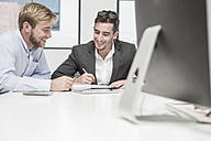 Two smiling businessmen having an office meeting - ZEF004535