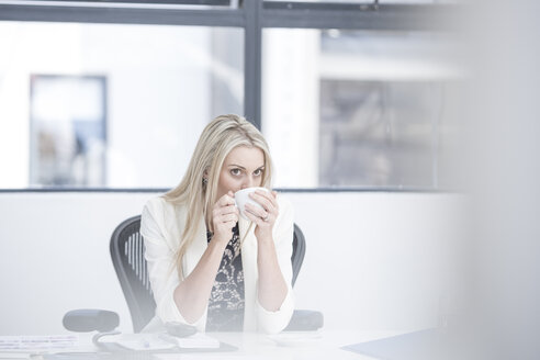 Businesswoman drinking coffee at her desk - ZEF004565