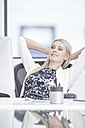 Businesswoman in office leaning back - ZEF004636