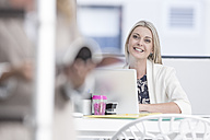 Portrait of smiling businesswoman in office with laptop - ZEF004647