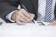 Close-up of businessman in office writing in organizer - ZEF004655