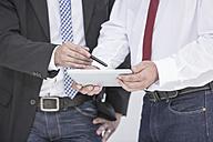 Close-up of two businessmen sharing digital tablet - ZEF004660