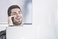 Smiling businessman in office with laptop and cell phone - ZEF004666