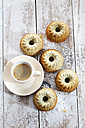 Five mini Gugelhupf with poppy seed and cup of coffee on wood - CSF024901