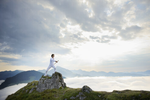 Austria, Kranzhorn, Mid adult woman exercising stick fighting on mountain top - MAOF000056