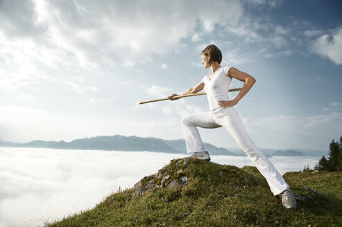 Austria, Kranzhorn, Mid adult woman exercising stick fighting on mountain top - MAOF000058