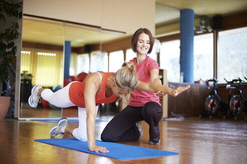 Woman exercising with coach in fitness studio - MAOF000078