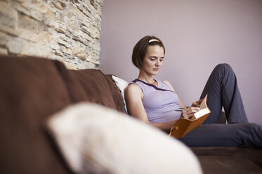 Woman sitting on couch taking notes - MAOF000013