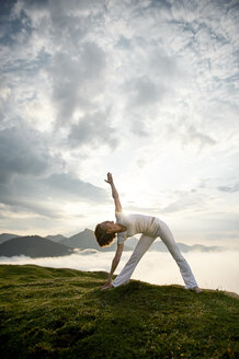 Austria.Kranzhorn, Mid adult woman practising yoga on mountain top - MAOF000020