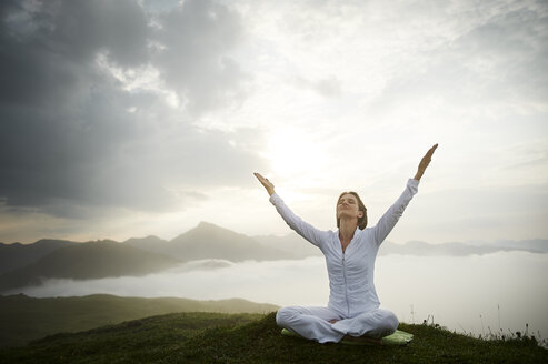 Austria.Kranzhorn, Mid adult woman practising yoga on mountain top - MAOF000022