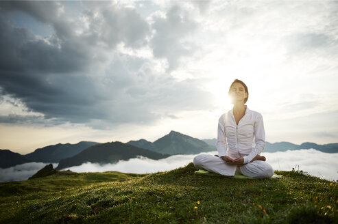Austria.Kranzhorn, Mid adult woman practising yoga on mountain top - MAOF000023