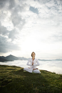 Austria.Kranzhorn, Mid adult woman practising yoga on mountain top - MAOF000024