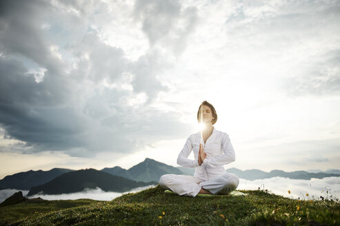 Austria.Kranzhorn, Mid adult woman practising yoga on mountain top - MAOF000025