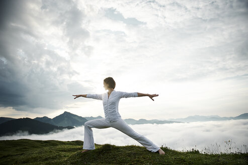 Austria.Kranzhorn, Mid adult woman practising yoga on mountain top - MAOF000026