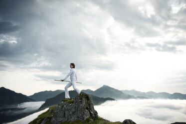 Austria, Kranzhorn, Mid adult woman exercising stick fighting on mountain top - MAOF000035