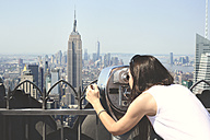 USA, New York, woman looking through binoculars on Manhattan with Empire State Building - GEMF000113