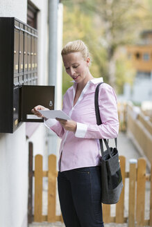 Woman standing in front of mailbox watching letter - NNF000197