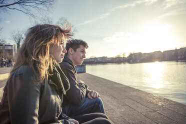 Germany, Berlin, teenage couple sitting at lakeshore in the late afternoon - MMFF000530