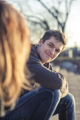 Germany, Berlin, portrait of smiling teenage boy watching his girlfriend - MMFF000522