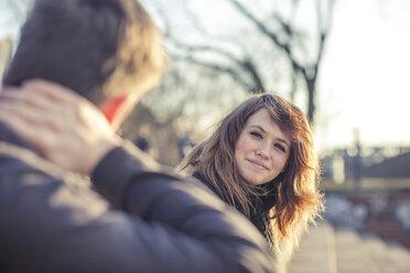 Germany, Berlin, portrait of smiling teenage girl watching boyfriend - MMFF000523