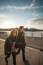 Germany, Berlin, teenage couple walking on a promenade along a lake - MMFF000524