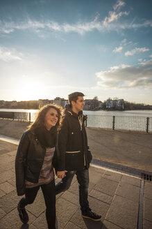 Germany, Berlin, teenage couple walking on a promenade along a lake - MMFF000524