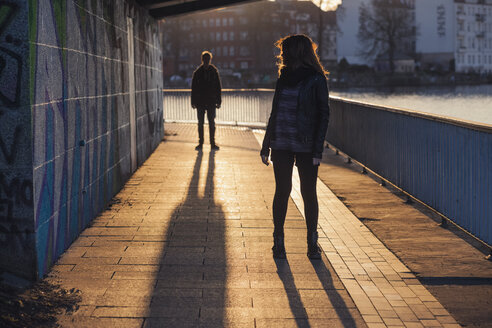 Germany, Berlin, teenage couple standing under a bridge at evening sunlight - MMFF000529