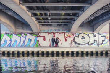 Germany, Berlin, teenage couple leaning at graffiti wall under a bridge - MMFF000516