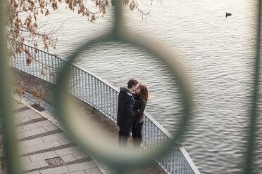 Germany, Berlin, teenage couple kissing on a promenade at a lake - MMFF000515