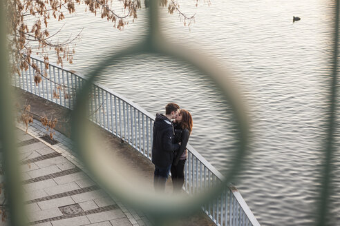 Germany, Berlin, teenage couple kissing on a promenade at a lake - MMFF000515