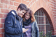 Teenage couple standing in front of a brick house watching smartphone - MMFF000509