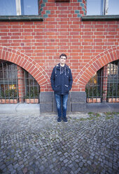 Teenage boy standing in front of a brick house - MMFF000508