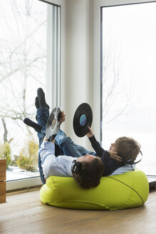 Father and son with records in living room listening music - JTLF000070