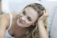 Portrait of smiling blond woman lying on a couch - ZEF003622