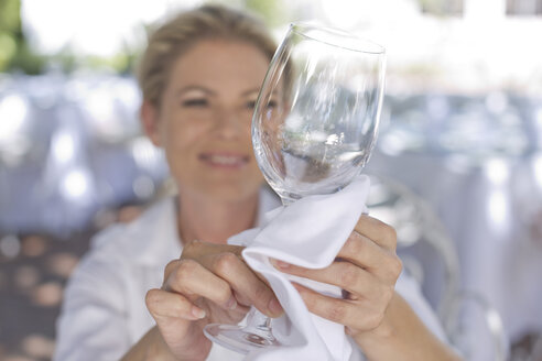 Waitress cleaning a wine glass with a cloth - ZEF004019