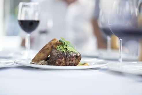Steak and red wine on table in restaurant - ZEF004091